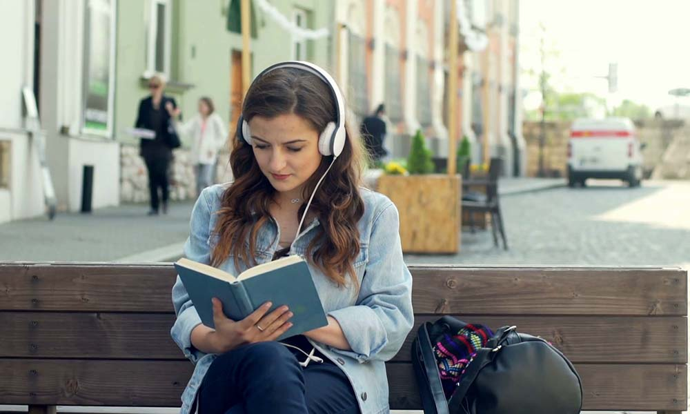 pretty-girl-listening-music-on-headphones-while-reading-book-on-the-bench_rdgyfdcpc_thumbnail-full01